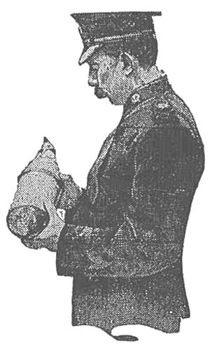 Chief of Police of King's Lynn, England, examining unexploded shell dropped in German air raid.